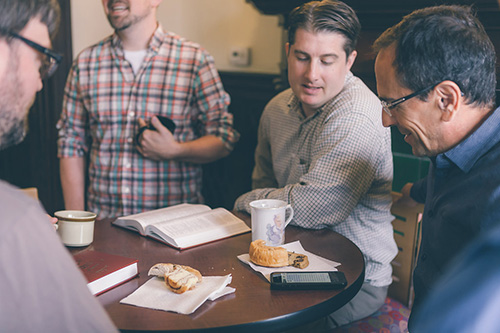 Group of men studying the bible while eating coffee cakes and drinking coffee